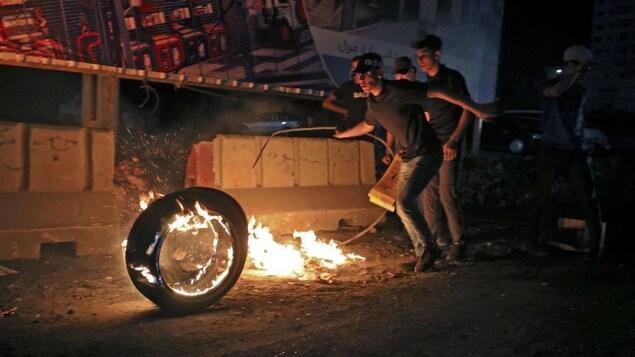 De jeunes hommes atour d'un pneu enflammé, à la nuit tombée.