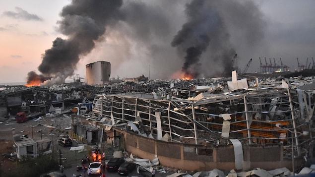 Des colonnes de fumée s'élèvent dans le ciel gris au-dessus de bâtiments ravagés.
