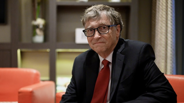 Bill Gates, assis sur un divan, regarde la caméra.