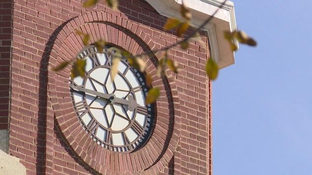 Horloge au sommet d'un immeuble en brique.