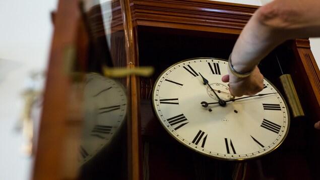 Une main qui tourne une clé dans une horloge afin d'en remonter le mécanisme.