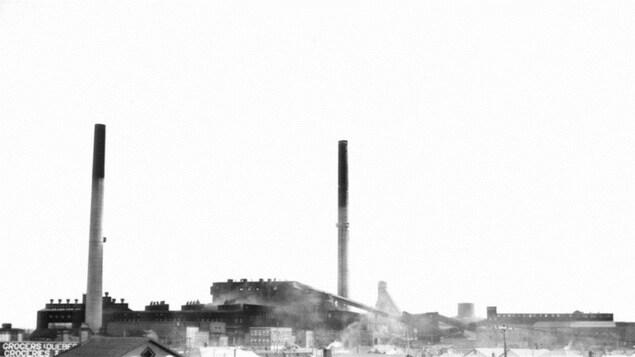 Vue du quartier des ouvriers à Noranda. À gauche, on aperçoit le bâtiment du Northland Grocers (Québec) Limited. À l'arrière-plan, on retrouve la mine Noranda et les chevalements de la mine Horne.