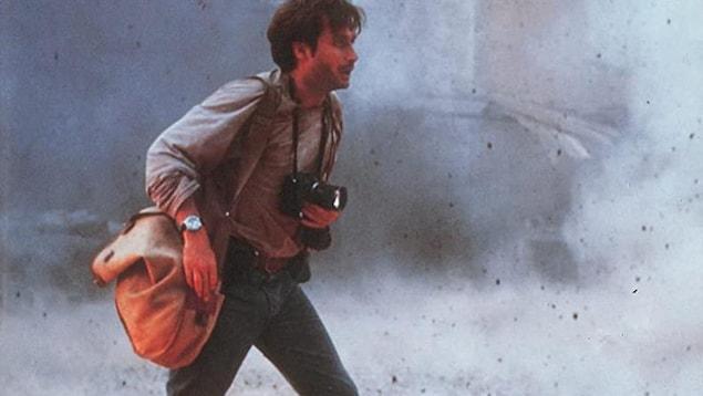 Un homme marche dans la rue où il y a de la fumée. Il a une caméra autour du cou.
