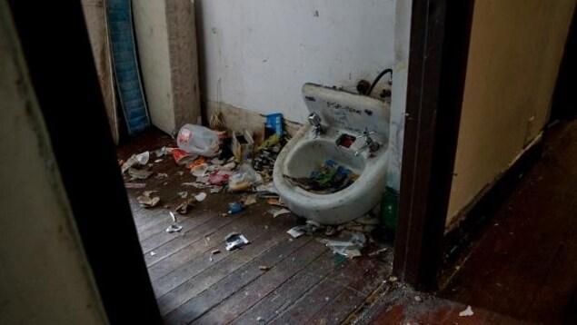 On voit un évier brisé très sale et le sol d'une pièce rempli d'ordures.