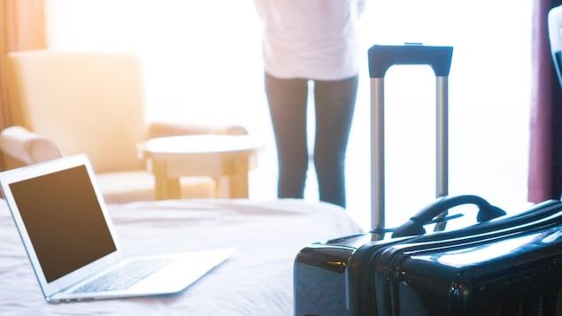 Une photo montrant une femme de dos en train de regarder à la fenêtre de son hôtel. En avant-plan, on peut voir une valise et un ordinateur portable posé sur le lit.