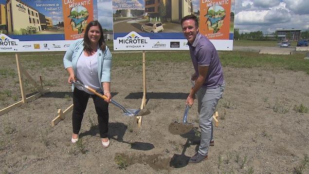 Julie Morin, mairesse de Lac-Mégantic, et Mathieu Mault, président de Activar avec des pelles remplies de terre devant une affiche qui annonce le nouveau complexe hôtelier de Lac-Mégantic.