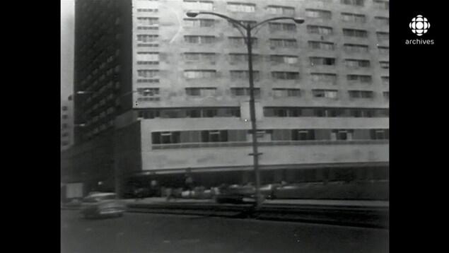En noir et blanc, façade de l'hôtel Le Reine Elizabeth, vu de l'autre côté de la rue, avec des voitures qui circulent.
