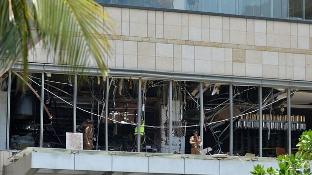 Des policiers se tiennent devant l'hôtel Shangri-La, dont les vitres ont toutes été détruites par l'impact de l'explosion.