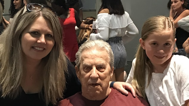 Trois personnes posent pour la photo. Au milieu, un homme âgé est assis. Sa fille est à sa gauche et sa petite-fille à sa droite.