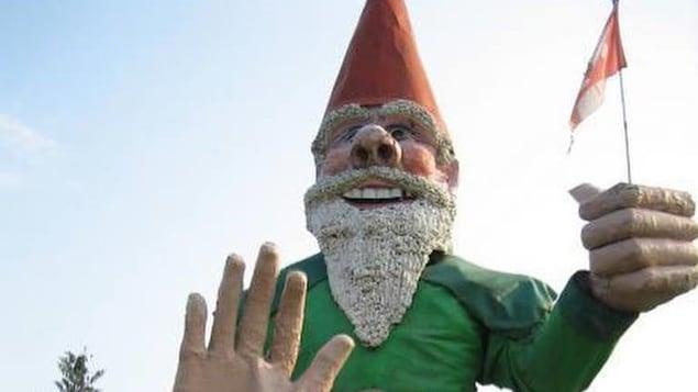 Le visage souriant de la statue, avec un poing dans lequel se trouve un drapeau canadien