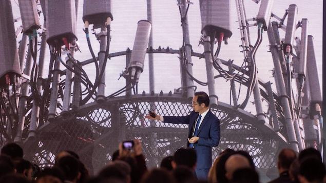 Un homme tend la main vers une présentation vidéo d'une tour de télécommunication devant plusieurs journalistes.