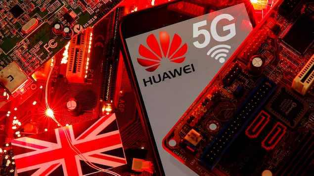 Le drapeau britannique et un téléphone intelligent avec le logo de Huawei et du réseau 5G visibles sur une carte mère de PC.