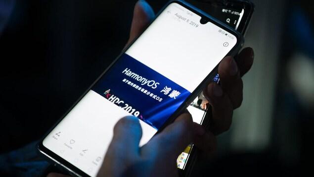 HarmonyOS est écrit sur l'écran d'un téléphone intelligent tenu par une main.