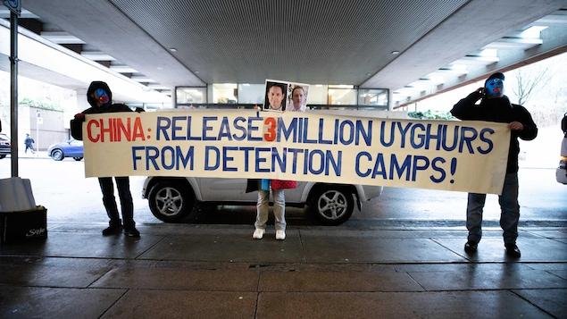 Tres personas sostienen una pancarta en la que se pide a China que libere a los uigures recluidos en campos.