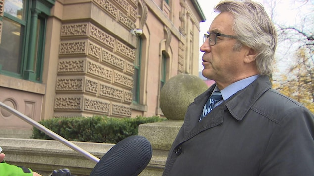Un homme donne une entrevue au micro devant le palais de justice.