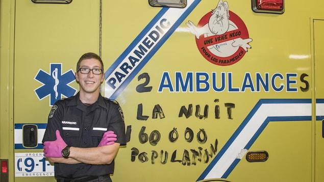 Un homme debout devant une ambulance de couleur jaune.