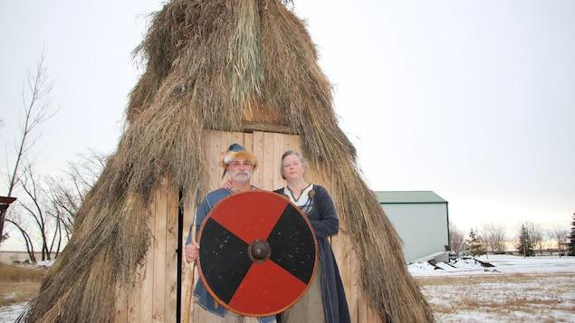 Wendy Speary et Pedro Bedard devant leur hutte avec des vêtements et accessoires du temps des Vikings.