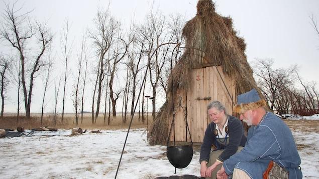 Wendy Speary et Pedro Bedard sont accroupis, près du feu et face à la hutte.