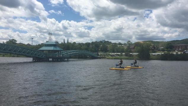 Deux résidents qui font l'essai de vélo d'eau sur la rivière Madawaska dans le secteur du centre-ville d'Edmundston.