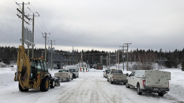 Des employés et des camions d'Hydro-Québec devant la sous-station de Rivière-Pentecôte.