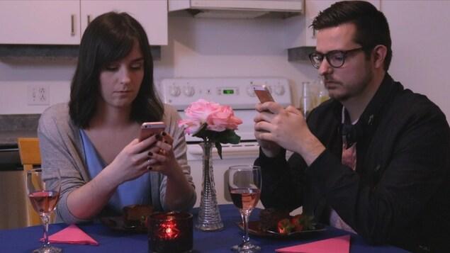 Des comédiens dans une scène de la pièce avec des téléphones intelligents.