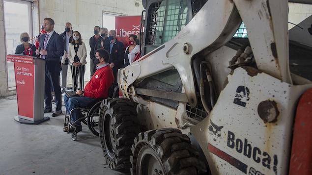 Iain Rankin prononce une allocution à côté d'une pelle mécanique sur un chantier.