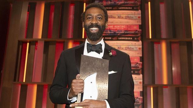 Ian Williams sourit, sur scène, un trophée dans les mains.
