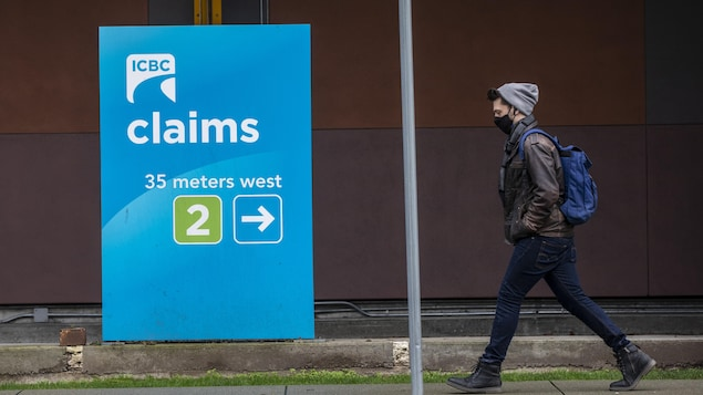 Une personne marche devant un centre de réclamation de ICBC à Vancouver.
