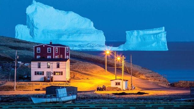 Deux maisons illuminées par la lumière jaunâtre des lampadaires, un bateau de pêche accosté sur le rivage et un énorme iceberg bleuté en arrière-plan.