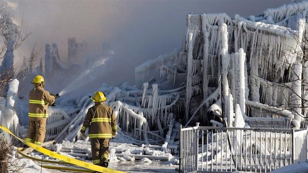 Pompiers devant les décombres de la Résidence du Havre de L'Isle-Verte, le 23 janvier 2014.
