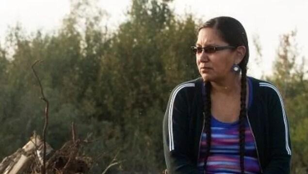 Une femme portant un chandail bleu et une veste noire est assise et regarde au loin
