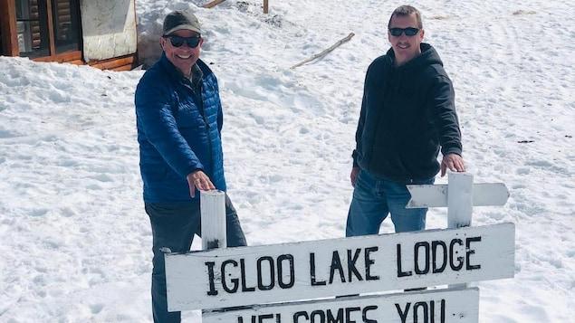 Deux employés devant une pancarte qui annonce le camp de pêche.