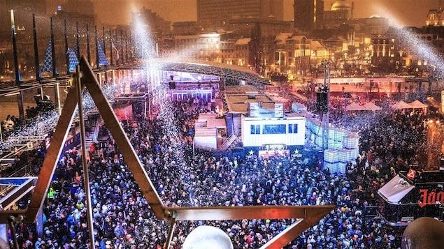 Une foule rassemblée devant une scène en plein hiver.