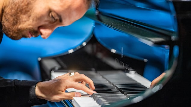 Un homme est penché sur son piano.