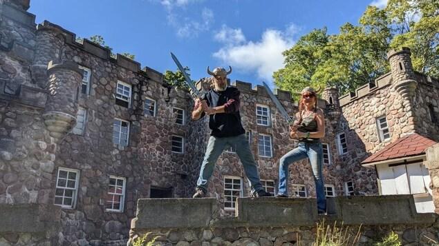 Un couple avec des fausse épées et des casques vikings font la pose devant un petit château de pierre.