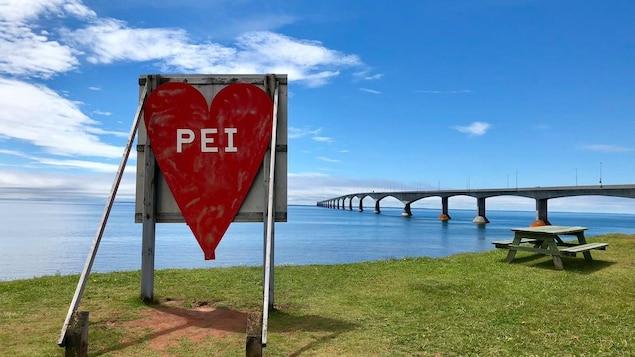 Une affiche en forme de coeur où sont inscrites les lettres « PEI », devant le pont de la Confédération.
