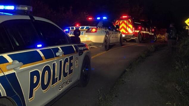 Deux voitures de police et un camion dsu Service des incendies de Gatineau sur un sentier étroit la nuit.