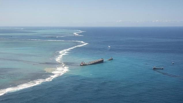 Le pétrolier en mer est incliné d'un côté. Deux bateaux plus petits sont à proximité.
