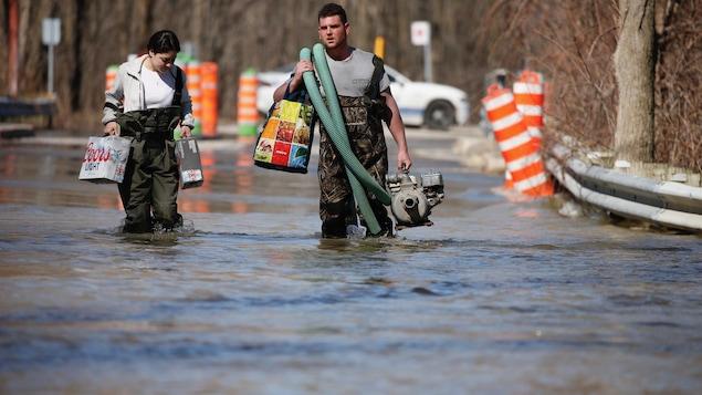 Un homme et une femme marchent dans l'eau. L'homme tient dans ses mains une pompe.