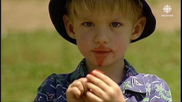 Visage d'un garçon qui mange une fraise.