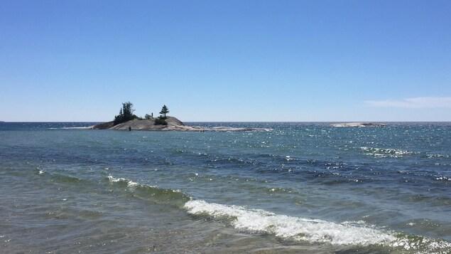 Des touristes marchent dans l'eau du lac Supérieur pour atteindre cet îlot rocheux pourvu d'une piscine naturelle réchauffée par le soleil.