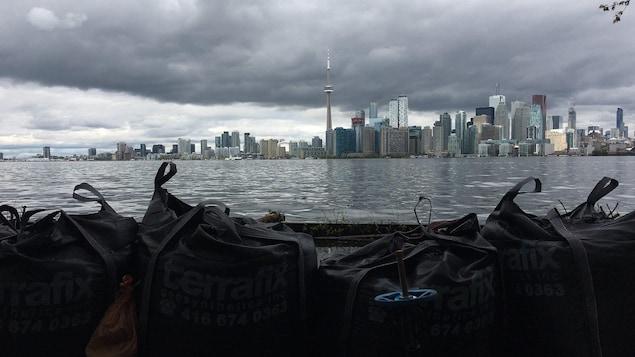 Des sacs de sable en premier blanc et Toronto en arrière-plan avec le lac Ontario au milieu.