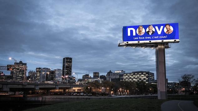 Un panneau avec la ville de Montréal en arrière-plan et le logo de Noovo avec trois personnalités.