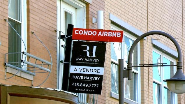 Une affiche annonçant la vente d'un condo destiné à la location Airbnb dans le quartier Saint-Roch, à Québec