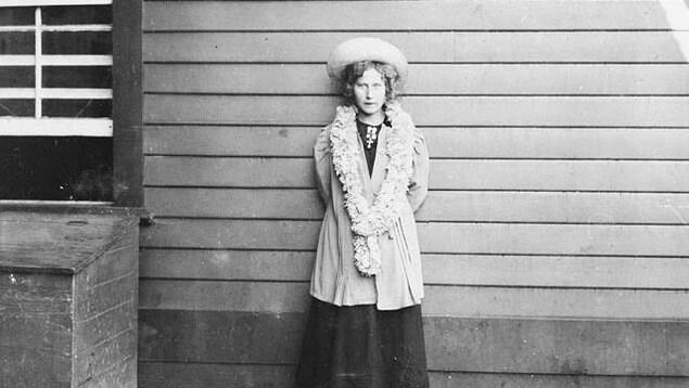 Une femme dans la vingtaine habillée sobrement, photo en noir et blanc