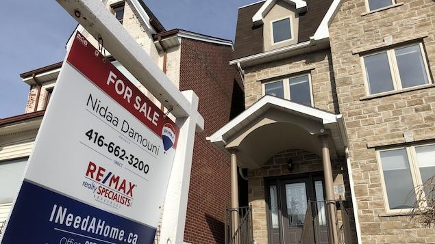 Une maison de trois étages avec une pancarte de vente.
