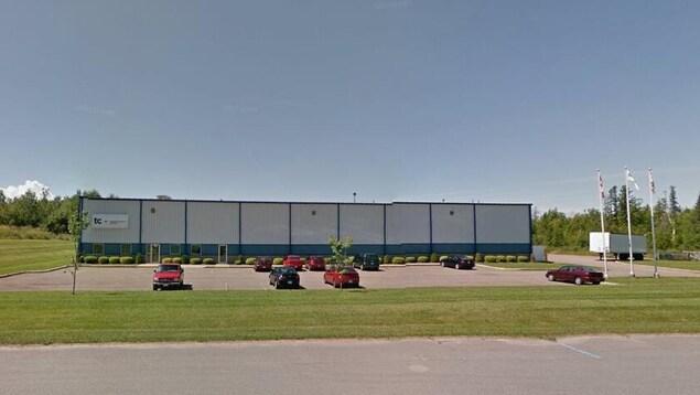 Photo du bâtiment de l'usine en été.
