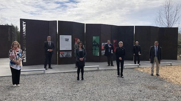Des représentants de Saguenay et de l'organisation des commémorations posent devant le monument rendant hommage aux victimes du glissement de terrain.