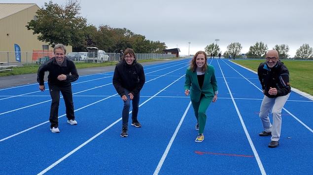 Daniel Drapeau, Chantal Pilon, Annie Thivierge et Marc Parent sont sur la piste d'athlétisme, en position pour démarrer une course.