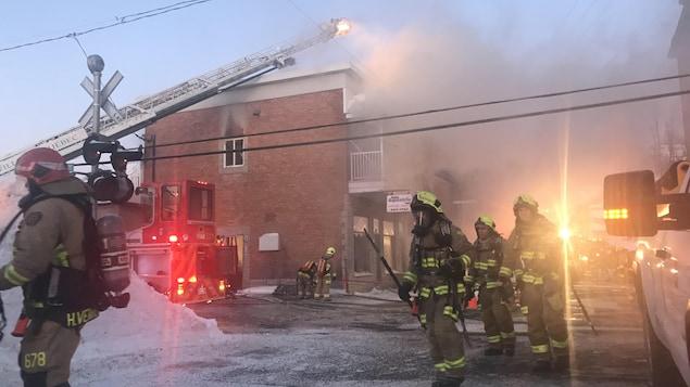Au moins une cinquantaine de pompiers combattent les flammes par temps froid.